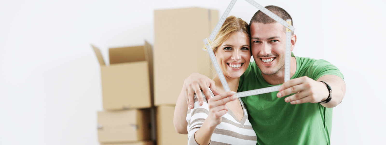 happy couple holding rulers in the shape of house in front of moving boxes